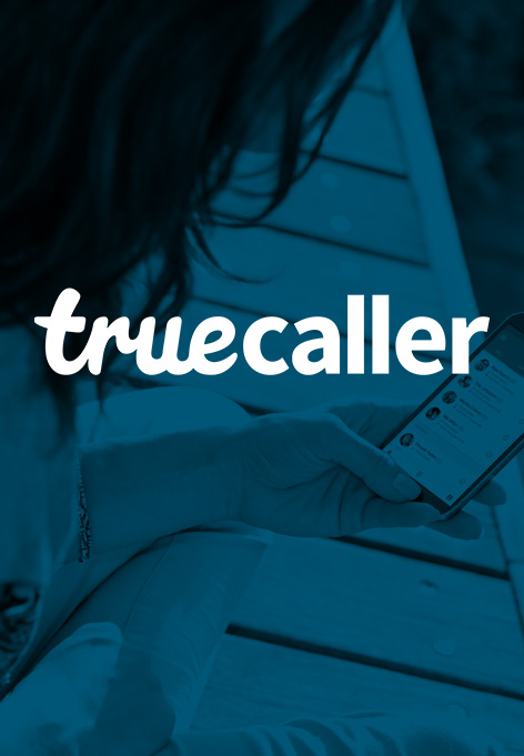 A woman holding a smartphone in her hand. Above is a text saying Truecaller.